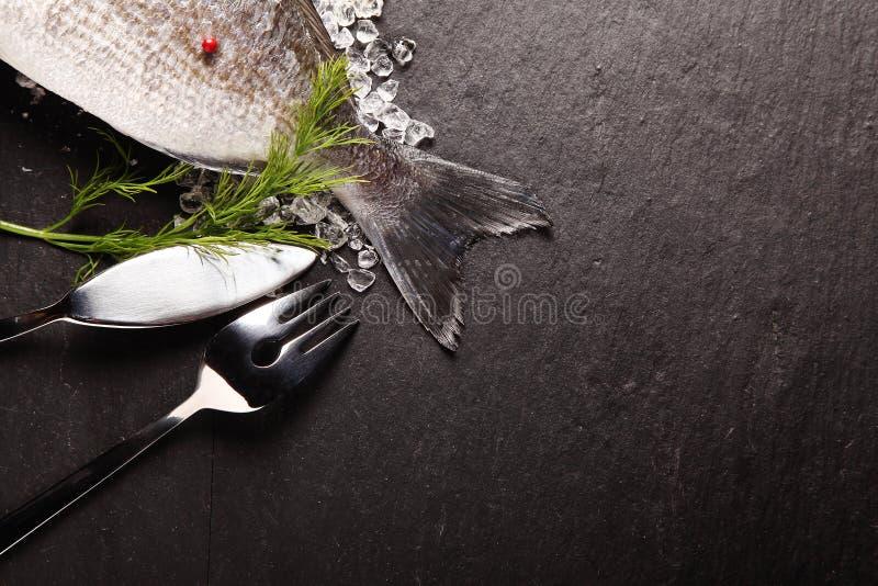 Peixes frescos no gelo com cutelaria fotos de stock royalty free