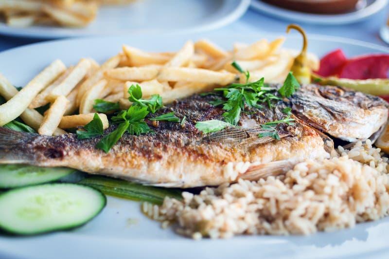 Peixes fritados com as batatas com vegetais em uma placa branca na taberna grega tradicional imagem de stock royalty free