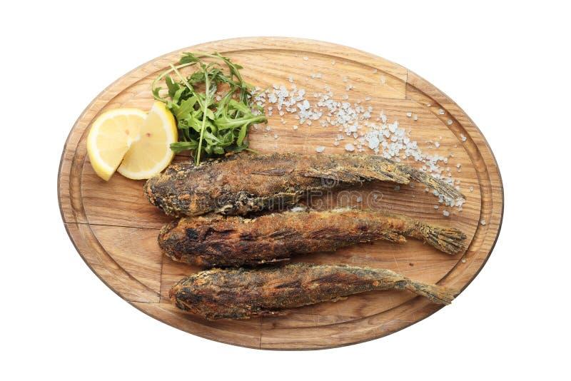 Peixes fritados em uma placa de madeira isolada no fundo branco fotos de stock