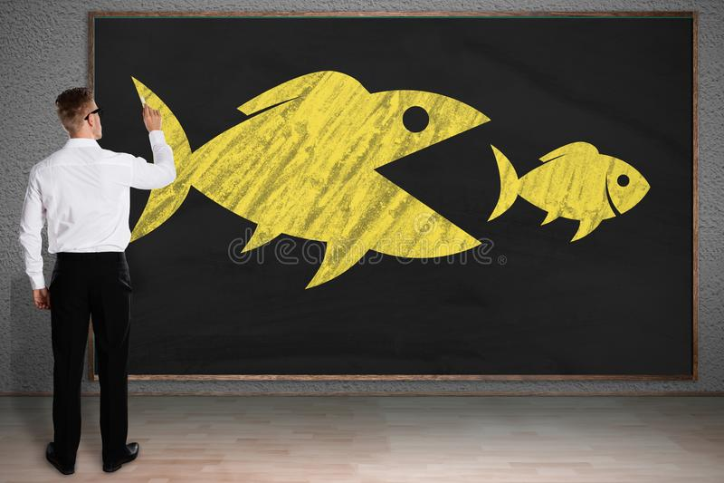 Peixes grandes de Drawing Sketch Of do homem de neg?cios que comem peixes pequenos foto de stock royalty free