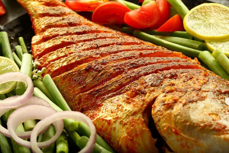 Peixes grelhados deliciosos com saladas frescas imagens de stock