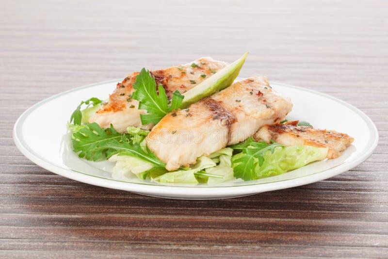 Peixes grelhados e salada fresca. fotografia de stock royalty free