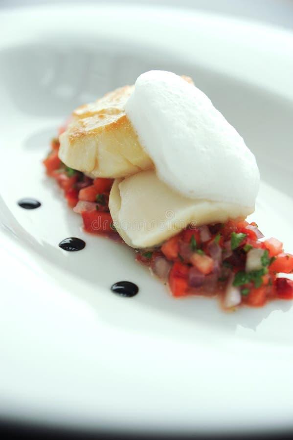 Peixes grelhados sobre a salsa do tomate fotografia de stock royalty free