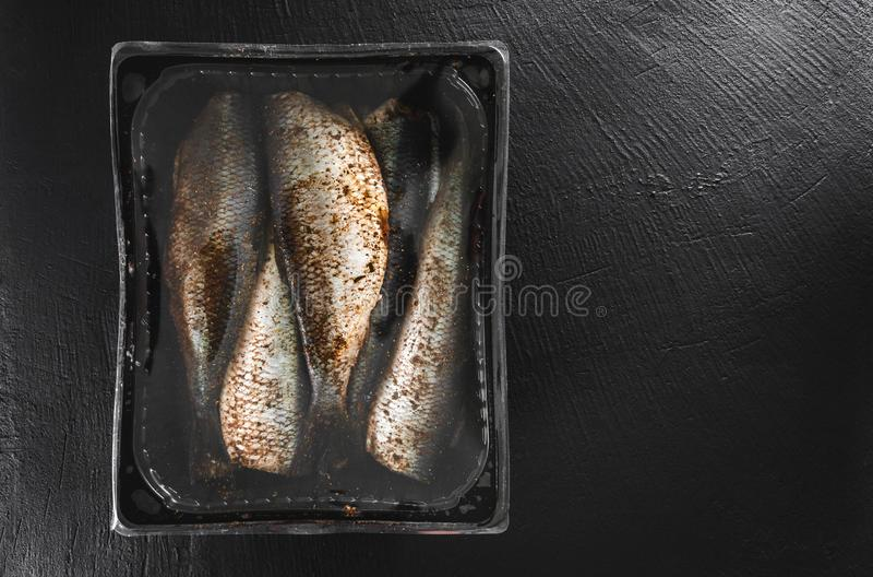 Peixes postos de conserva da cavala ou dos arenques com as especiarias embaladas na caixa no fundo da pedra da ardósia Alimento m imagem de stock royalty free
