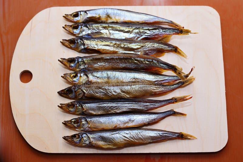 Peixes salgados secados em uma placa de corte foto de stock royalty free