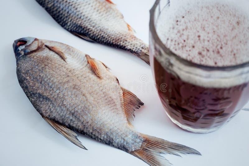 Peixes secados na tabela e em um vidro da cerveja imagem de stock