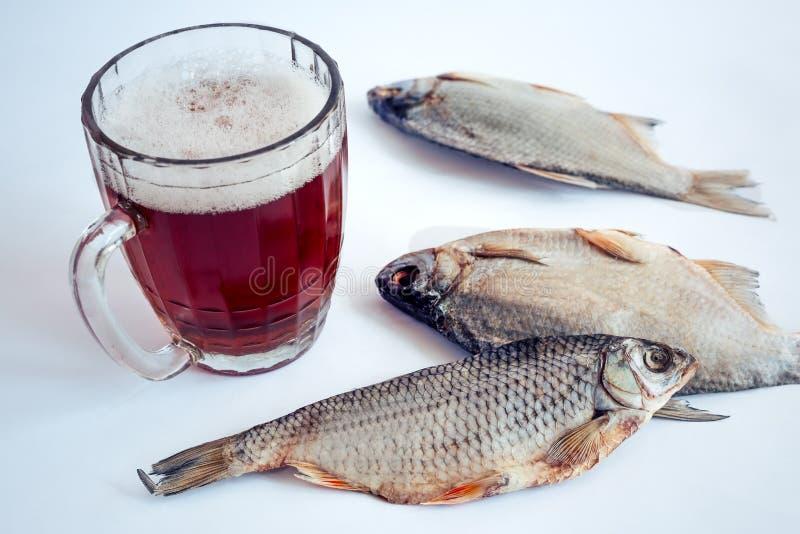 Peixes secados na tabela e em um vidro da cerveja foto de stock