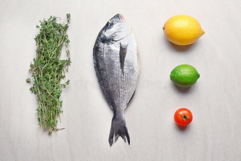 Peixes, tomilho, citrinas e tomate frescos do dorado imagem de stock