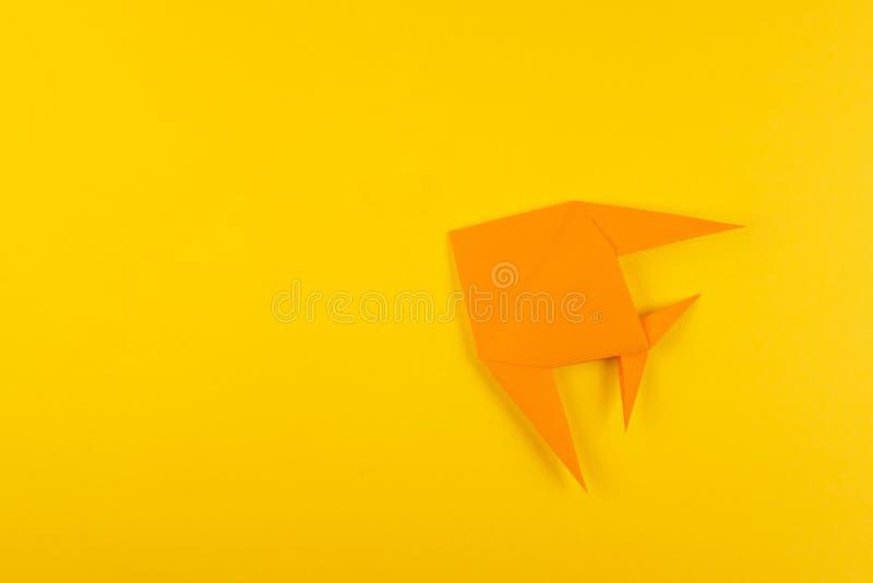 Peixes tropicais do origâmi no fundo minimalistic amarelo fotos de stock