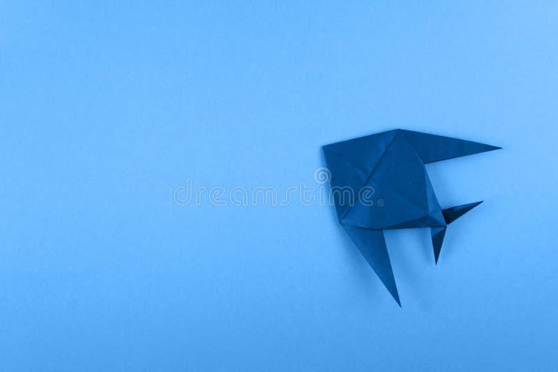 Peixes tropicais do orig?mi no fundo minimalistic dos azul-c?u fotografia de stock