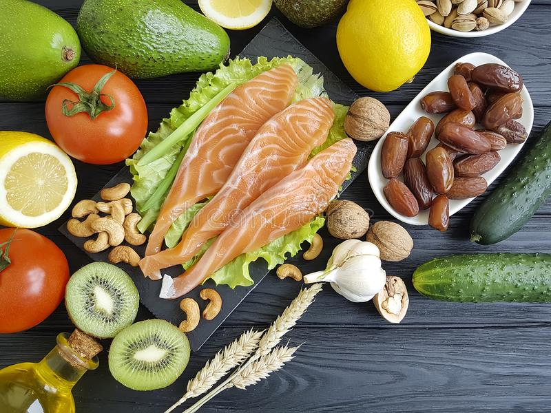 Peixes vermelhos, do jantar nuts da seleção do abacate pepino sortido natural no alimento de madeira, saudável preto foto de stock