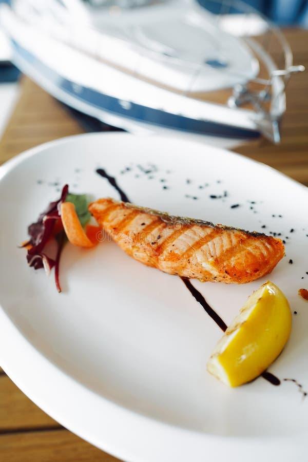 Peixes vermelhos grelhados deliciosos em uma placa branca fotos de stock