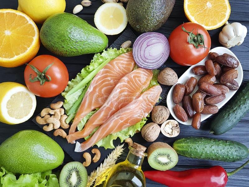 Peixes vermelhos, pepino nuts do jantar da seleção do abacate no alimento de madeira, saudável preto fotos de stock royalty free