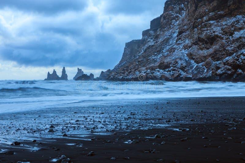 Pejzaż z plażą czarnego piasku, dramatyczne niebo i stosy morskie w tle na zmierzchu zimą, Reynisdrangar ne zdjęcie stock
