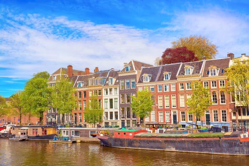 Pejzażu miejskiego widok kanał Amsterdam w lecie z niebieskim niebem, domowymi łodziami i tradycyjnymi starymi domami, Malowniczy obraz stock