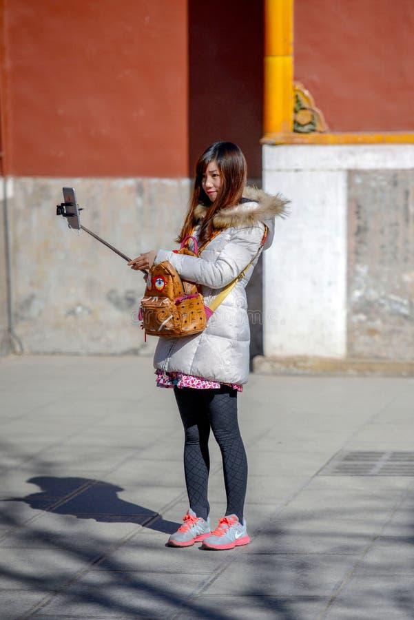 PEKÍN, CHINA - 10 DE MARZO DE 2016: Una chica joven fotografía el selfie fotos de archivo libres de regalías