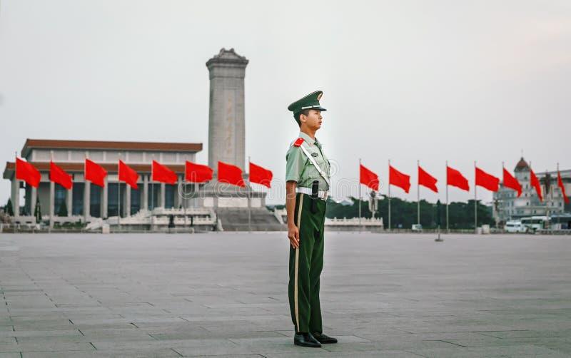 PEKÍN - CHINA, MAYO DE 2016: El soldado del guardia de honor en el chino de la Plaza de Tiananmen señala el fondo por medio de un fotos de archivo