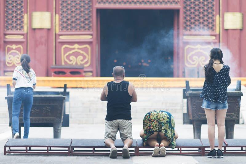Pekín, China - 08 01 2016: Pueblo chino que ruega delante de un templo en Pekín foto de archivo