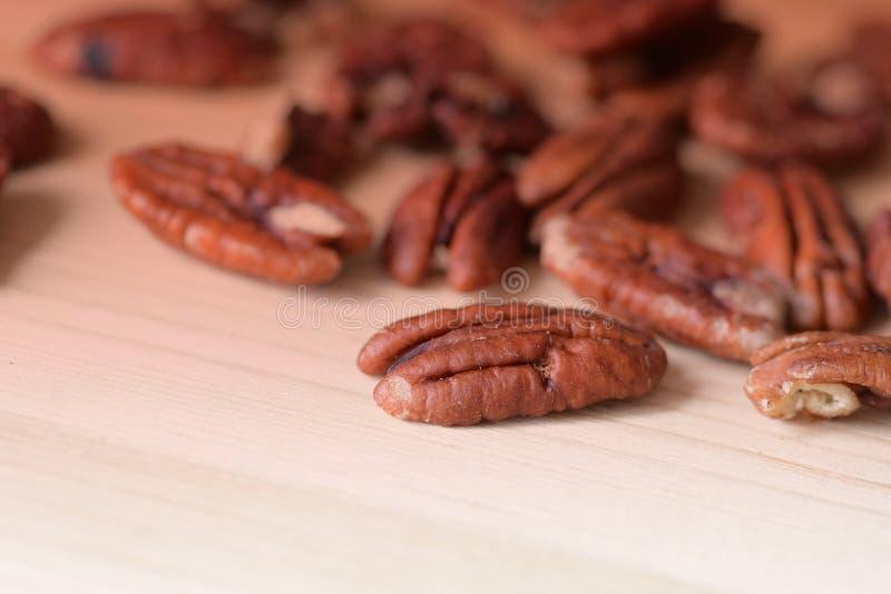 Pekanmutungen sind auf einer Holzfläche in der Nähe verstreut Gesunde Ernährung, braune Farbe lizenzfreie stockfotos