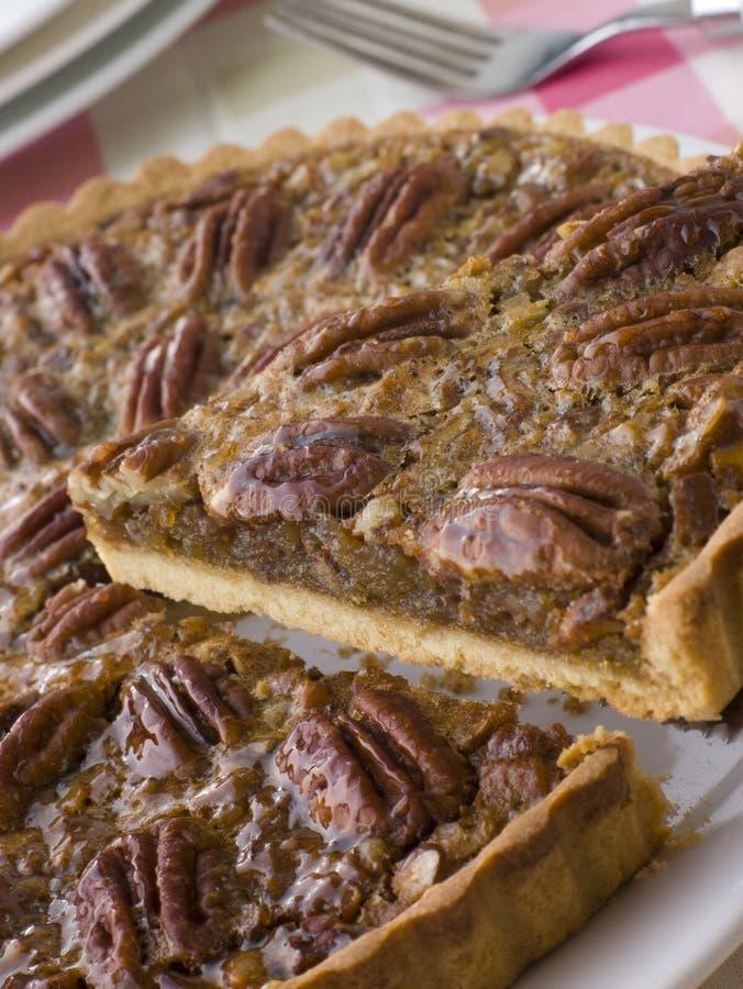 Pekannuss-Torte mit einer Scheibe, die geschnitten wird stockfotografie