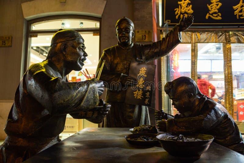 PEKING, CHINA - 21. DEZEMBER 2017: Asphaltieren Sie Skulptur einer Familie im Restaurant, das auf Qianmen-Straße gelegen ist stockbild