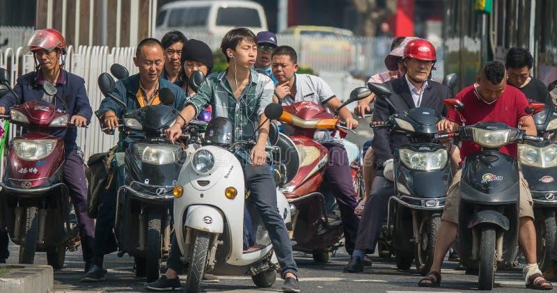 PEKING/CHINA-JULY 30 2017: Folk på sparkcyklar som väntar på trafikljusen i staden av Peking Endast bär några personer fotografering för bildbyråer