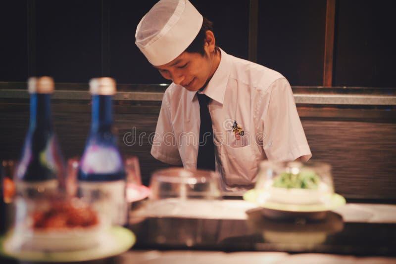 Peking, China - Juni 11, 2018: Een Chinese chef-kok kookt sushi voor de restaurantbezoekers royalty-vrije stock fotografie