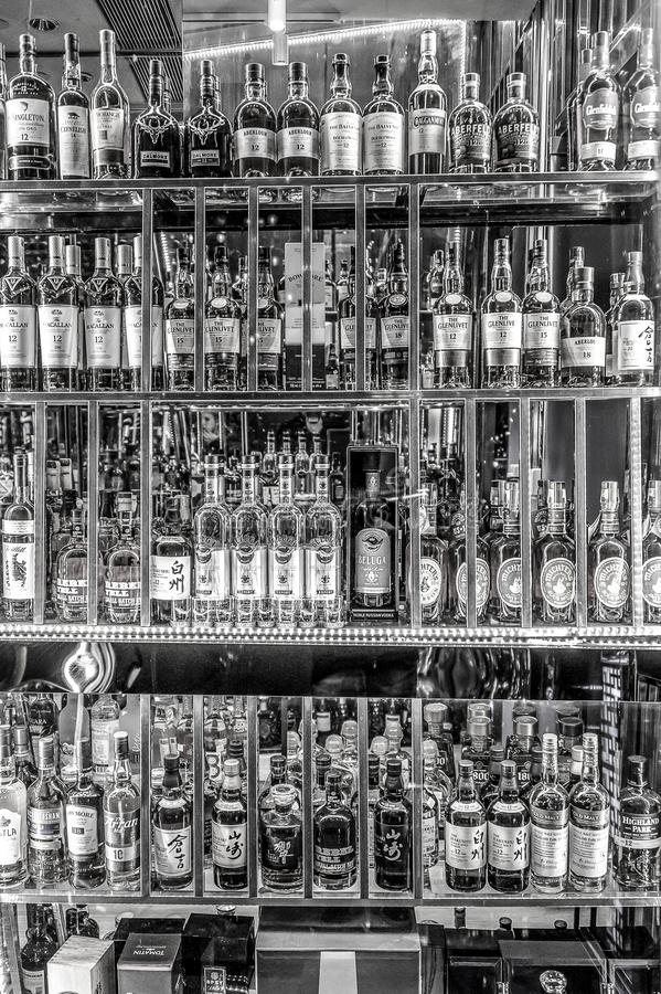 24.02.2019 Peking China - Wall with Bitters and alcohols whiskey bar counter bottles ambient tlight blurred background.  stock photography
