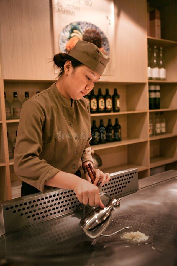 Peking Kina - Juni 9, 2018: En kinesisk kvinnlig kock lagar mat matställen framme av restaurangbesökarna fotografering för bildbyråer