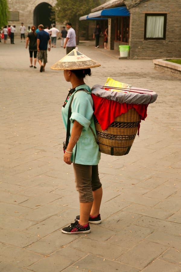 Peking Kina 10/06/2018 kinesiska kvinna för A i en triangulär hatt med en korg som binds på hennes baksida, väntar på turister royaltyfri fotografi