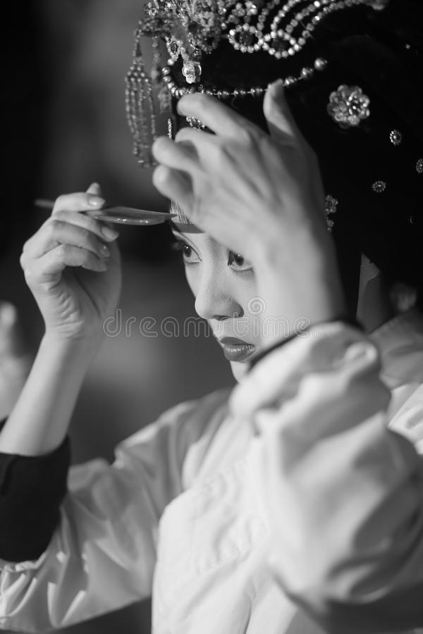 Peking opera actress makeup and comb hair. Before the performance, the chinese female peking opera performer makeup and comb her hair. black and white image royalty free stock photography