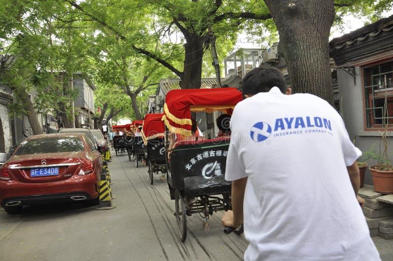 Peking 7th kan: Rad av trehjulingar med den röda taxin från Wangzuoen Hutong i Peking royaltyfria foton