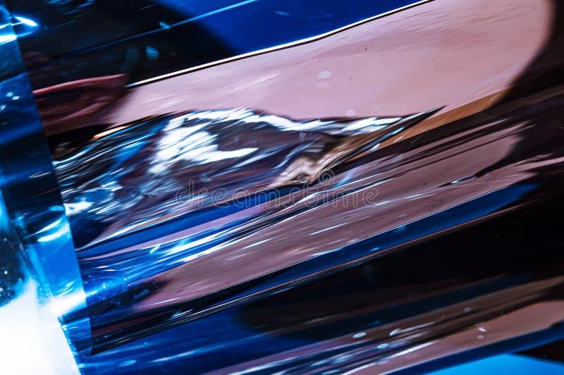 Película arrugada plástica olográfica con reflejos de luz del sol del contraste Tonos azules con las sombras negras oscuras foto de archivo libre de regalías