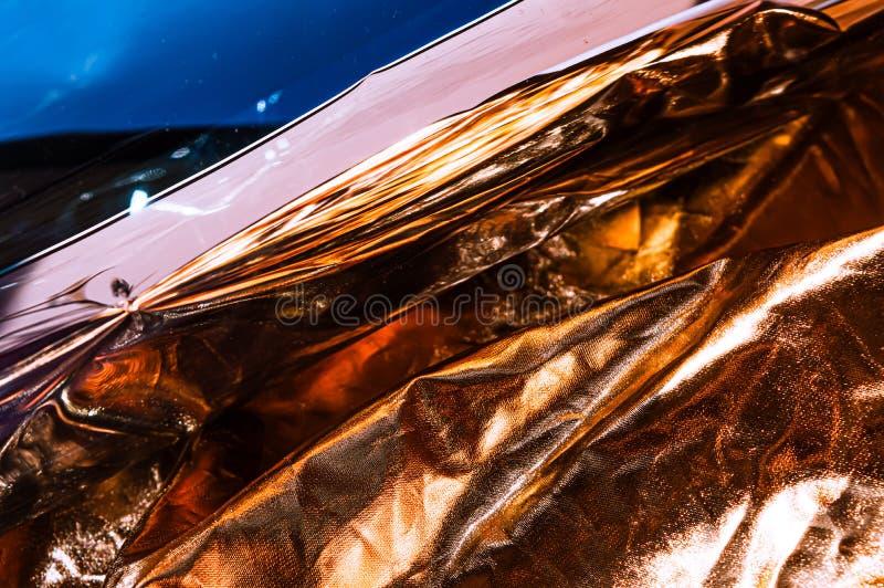 Película arrugada plástica olográfica con reflejos de luz del sol del contraste Tonos azules con las sombras negras oscuras imagen de archivo