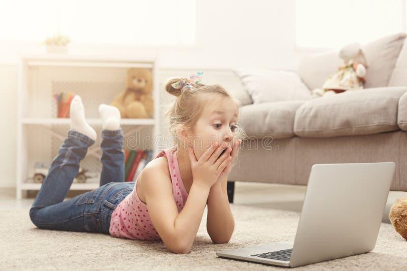 Película de observación asustada de la niña casual en el ordenador portátil mientras que miente en el piso en casa imágenes de archivo libres de regalías