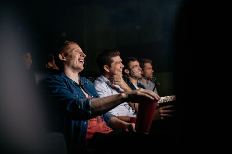 Película de observación de la comedia de la gente joven en teatro foto de archivo libre de regalías
