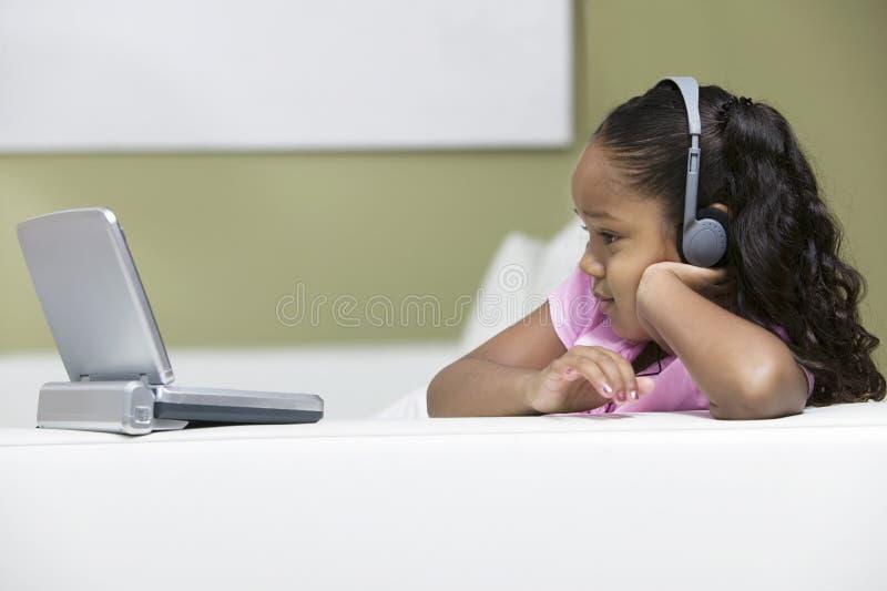 Película de observación de la muchacha en el reproductore de DVD portátil fotos de archivo