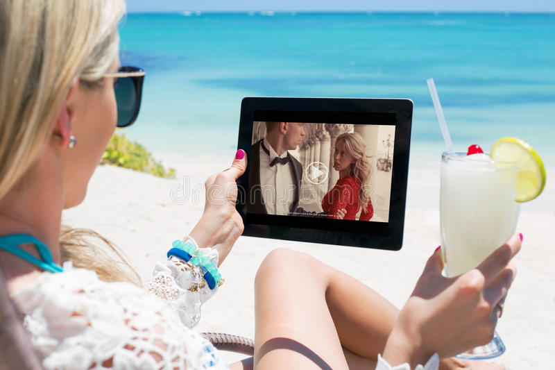 Película de observación de la mujer en la tableta foto de archivo