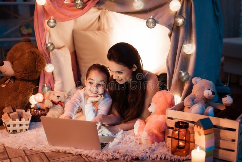 Película de observación de la madre y de la hija en el ordenador portátil en casa de la almohada tarde en la noche en casa imágenes de archivo libres de regalías