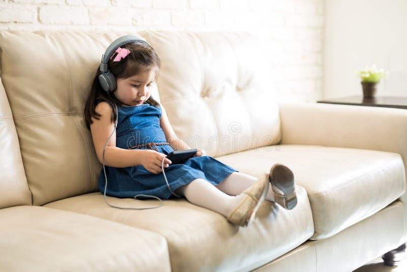 Película de observación de la muchacha bonita en smartphone imagen de archivo