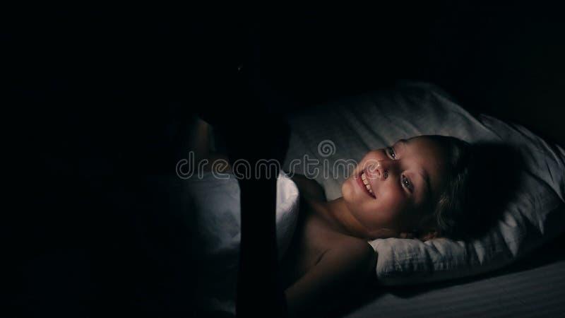Película de observación TV de la muchacha que ríe divirtiéndose en cama Muchacha adolescente caucásica rubia atractiva en cama en imagen de archivo libre de regalías