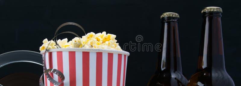 Película en palomitas, en un fondo negro, con dos botellas de cerveza foto de archivo libre de regalías