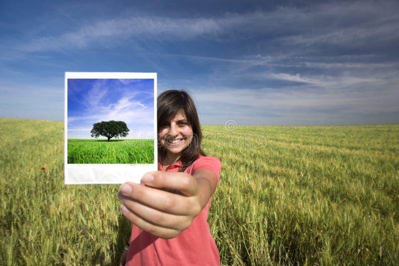 Película polaroid sonriente de la explotación agrícola de la mujer joven sola foto de archivo libre de regalías