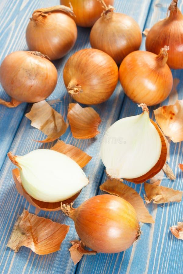 Peló cebollas frescas en los tableros azules, concepto sano de la nutrición fotografía de archivo libre de regalías