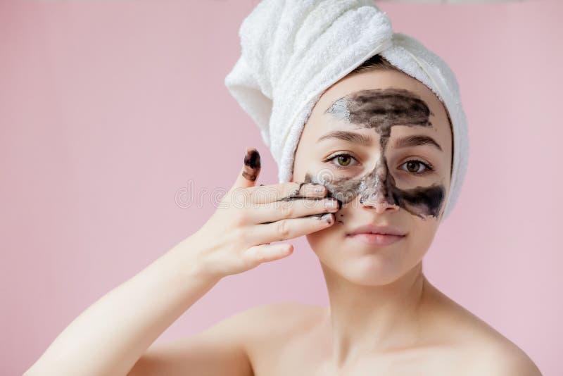 Peladura cosm?tica de la belleza La hembra joven hermosa del primer con negro pela apagado la m?scara en piel Primer de la mujer  imagen de archivo