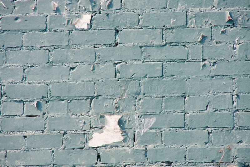 Peladura de la pintura azul en la pared de ladrillo vieja foto de archivo