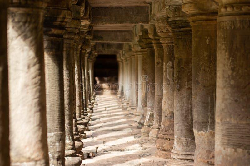 Pelare f?r forntida tempel under en g?ngbana i Angkor Thom, Cambodja royaltyfri foto