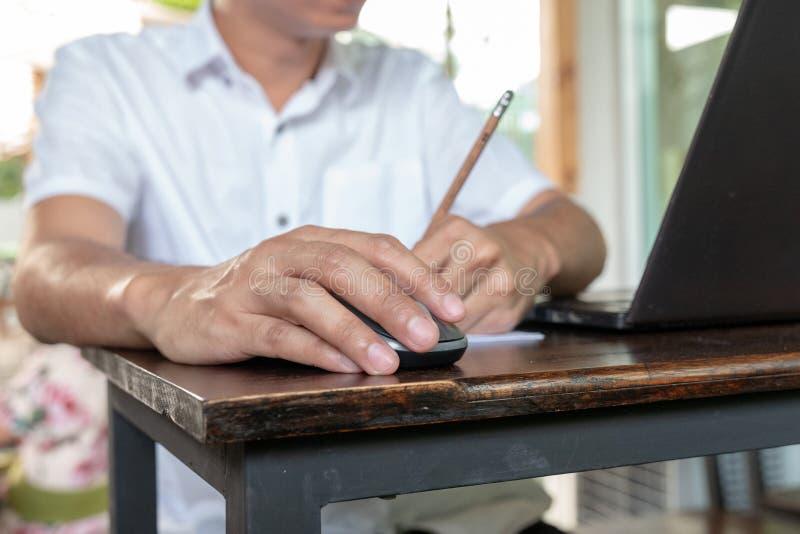 Pele bronzeado asiática que guarda o rato sem fio na tabela de madeira do vintage e que escreve o lápis com sua mão esquerda imagens de stock
