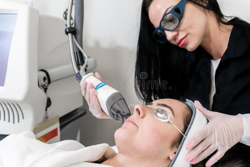 Pele de execução do técnico do laser da beleza que resurfacing o procedimento em uma clínica médica dos termas e da beleza Pacien fotos de stock