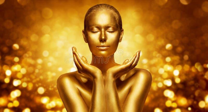 Pele de Ouro, Linda Mulher, Prendendo Beleza Dourada em Mãos, Fashion Art Make Up imagem de stock royalty free